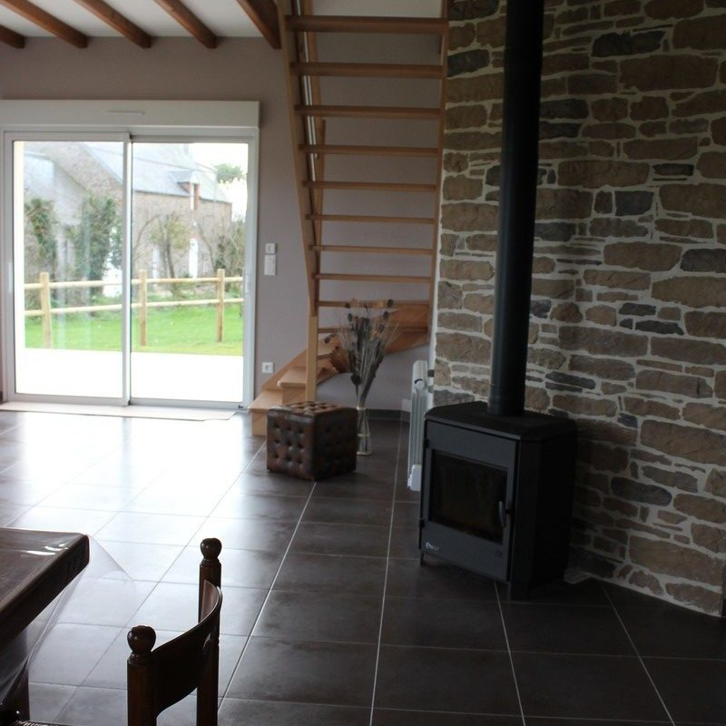 Pénétrez dans le salon ouvert sur la terrasse et lumineux grâce à deux grandes baies vitrées