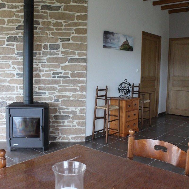 Découvrez la vaste pièce à vivre avec son espace salon salle à manger doté d'un poêle à bois